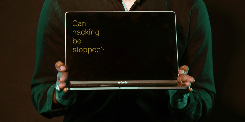 """man holding computer that reads """"can hacking be stopped?"""""""