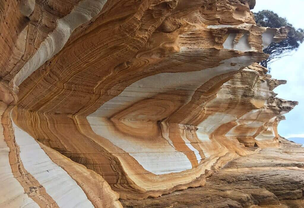 Painted cliffs with white and red circles of color in the stone