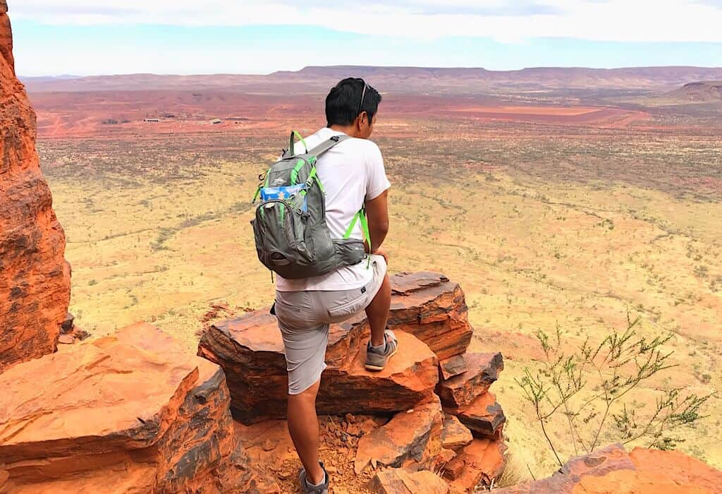 Trin standing on the trail leading to the top of Mount Bruce looking over the red landscape of Karijini National Park.
