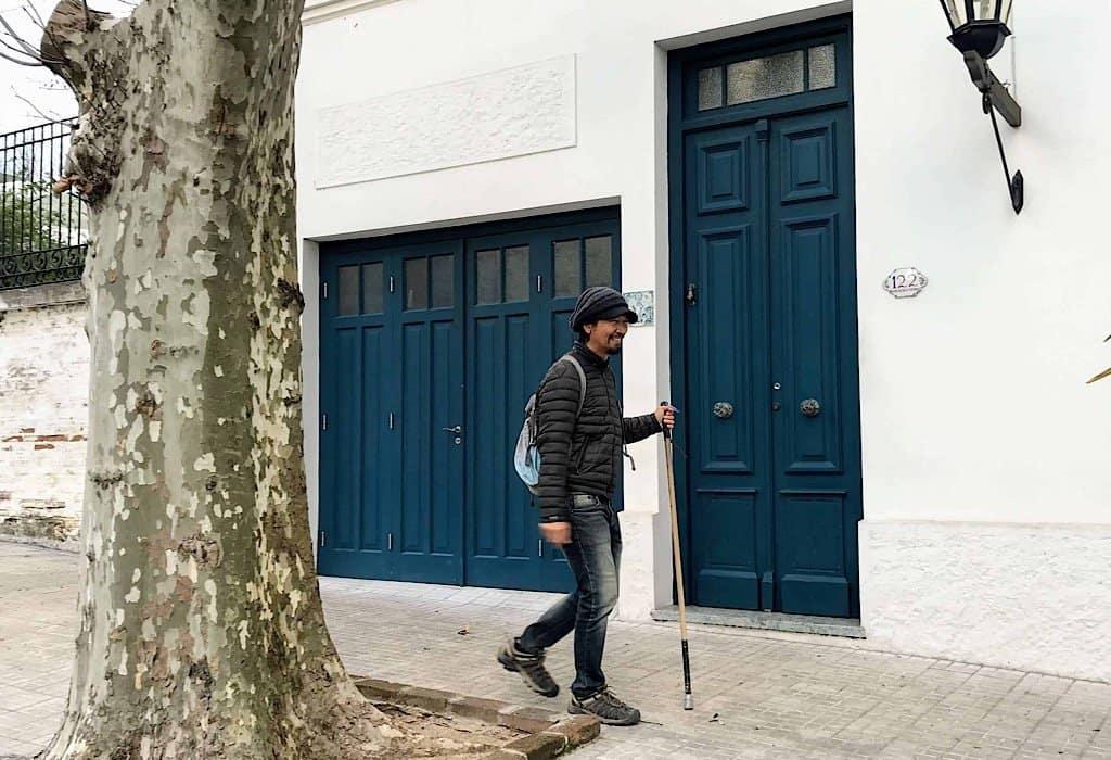 Trin walking by a blue door in Uruguay