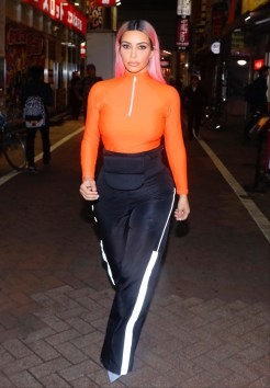 Kim Kardashian takes a night-time walk though Tokyo wearing a bright orange top. Poses for pictures with fans