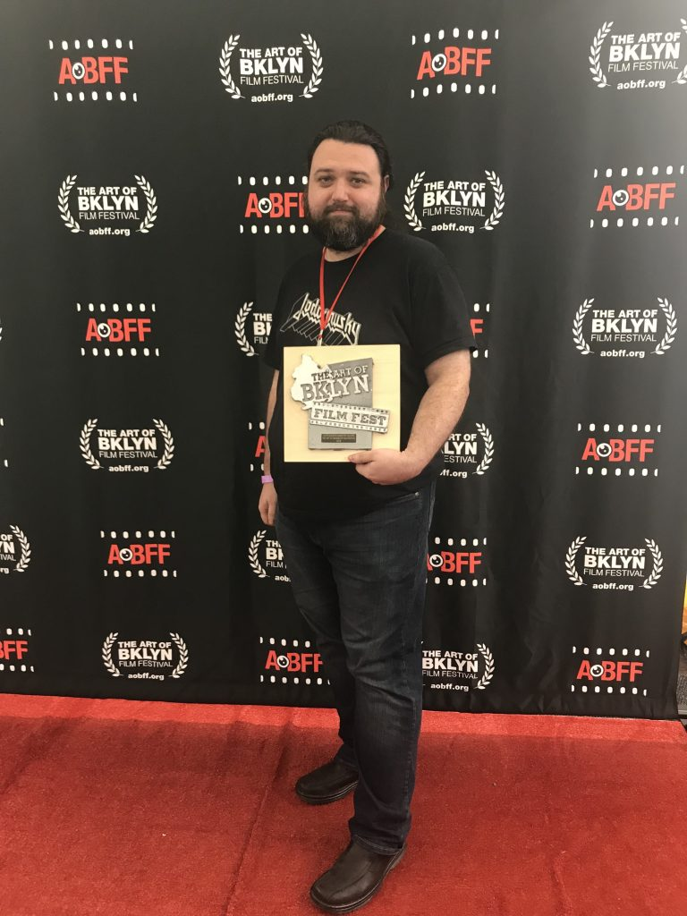 Director Sean Mannion holding the award for Outstanding Narrative Feature.