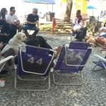 Aparece uma parte da galera e cães, estamos sentados no calçadão da praia formando uma roda
