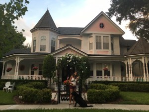 Estou em frente a uma grande casa rosa, parece casa de boneca, na frente possui um belo jardim