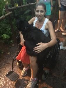 Foto da Mellina sentada na cadeira de rodas com a Hilary em seu colo