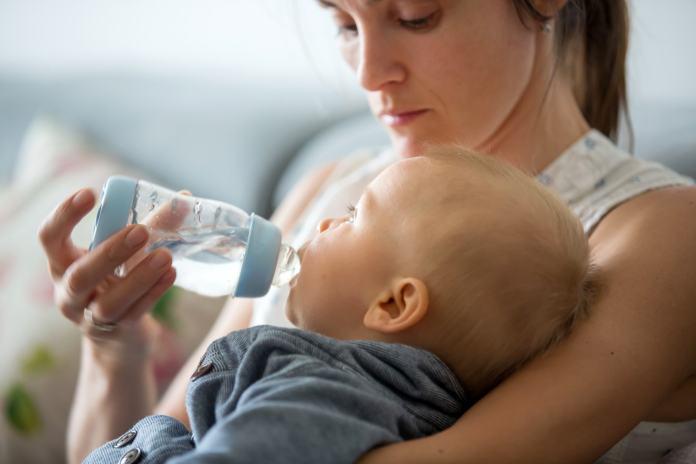 Mutter verabreicht ihrem Baby Wasser