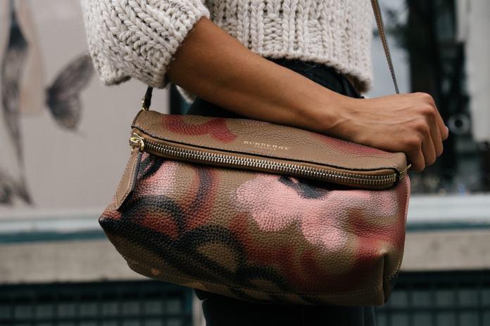 Frau mit einer braunen, bemalten Handtasche