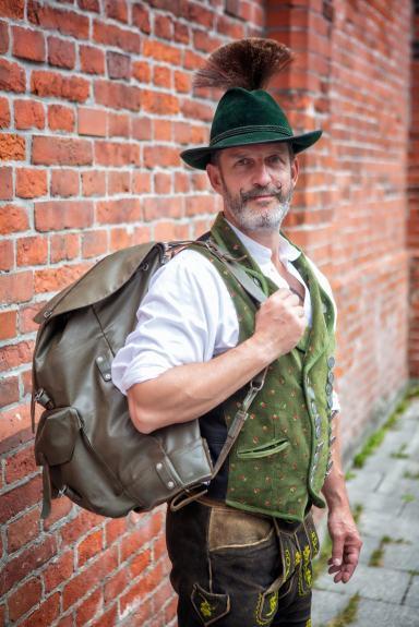 Mann in Ledertracht mit Rucksack