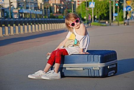 Kleines Mädchen sitzt auf Hartschalenkoffer