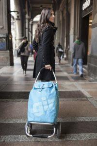 Junge Frau mit blauem Einkaufsroller
