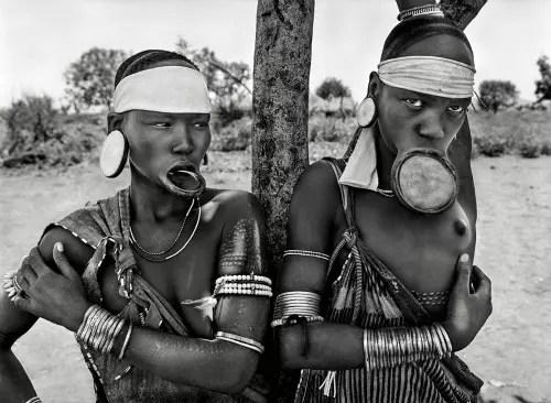 *Mulheres das aldeias de Mursi e Surma, no Parque Nacional de Mago, na Etiópia (2007). O uso de alargadores em formato de prato nos lábios é restrito às castas superiores