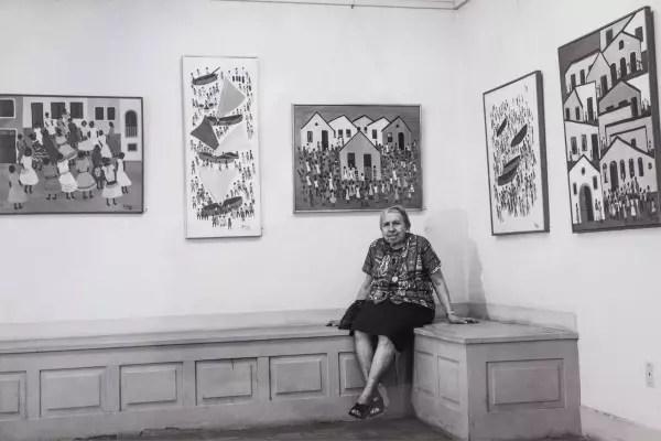 A pintora sentada entre seus quadros