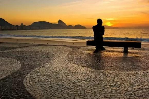 O sol nascendo no mar, atrás da estátua de Carlos Drummond, em Copacabana