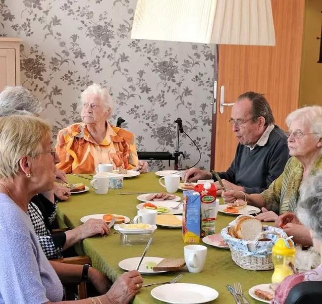Alguns dos velhos que vivem na vila fazendo refeição juntos