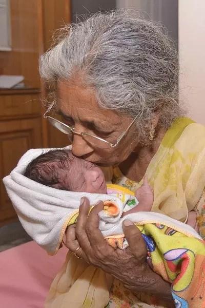 Mãe tardiamente, ela acaricia o filho nascido no mês passado