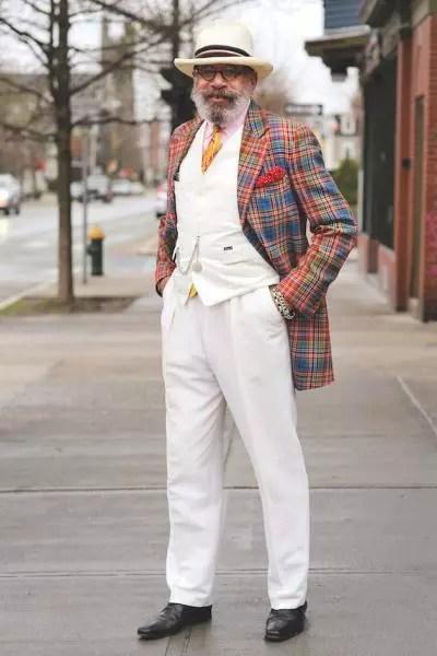 Calça e jaqueta brancas, com capote xadrez. Sem esquece o chapéu