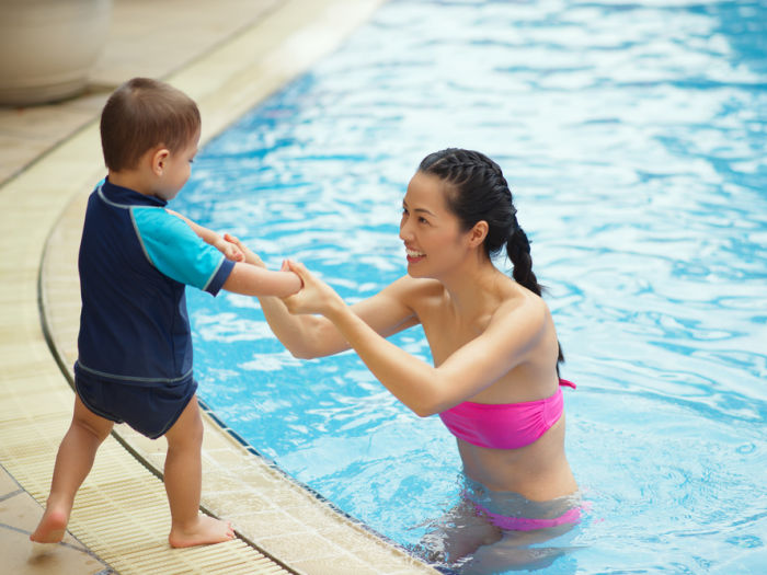 Chinese young woman teaching her son not to be afraid of water