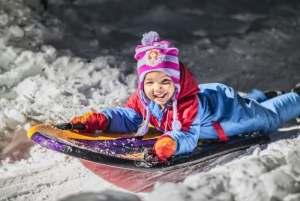kid sledding in the snow