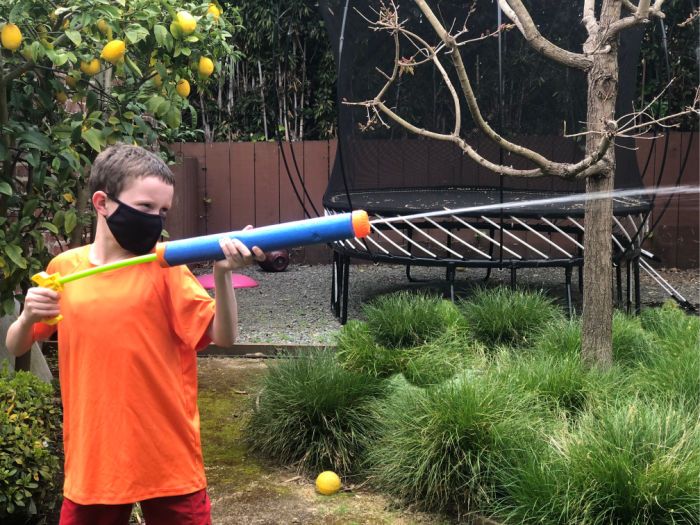 kid with squirt gun super soaker