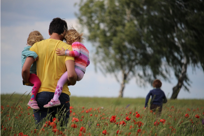 father carries two kids in field