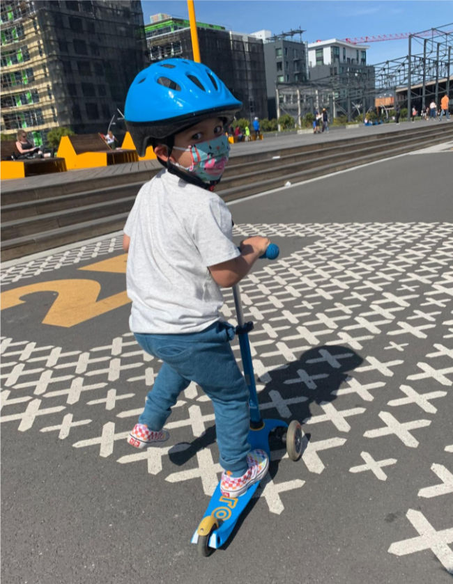 child on scooter with helmet