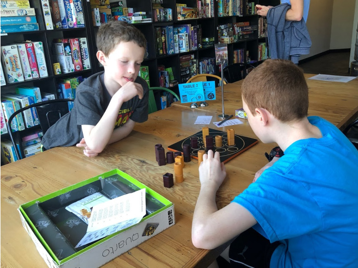 two kids play board games