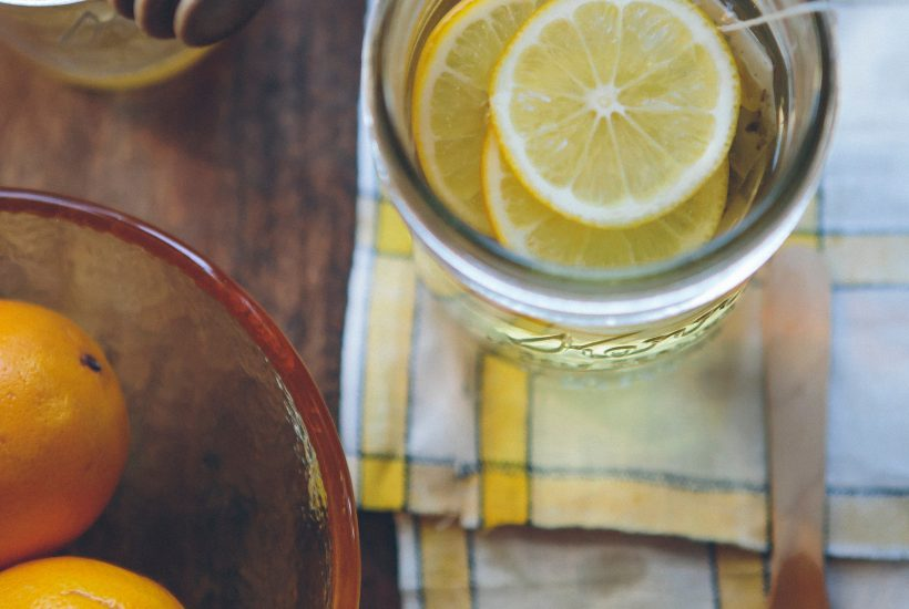 slices of lemon in glass on yellow and white dish cloth