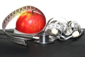 apple with stethoscope and measuring tape