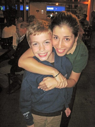 A small boy is hugged by a teenage waitress at the Smile Cafe in Athens.