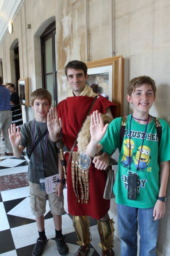 The author's children with a costumed actor doing the welcome greeting of the Roman Legion