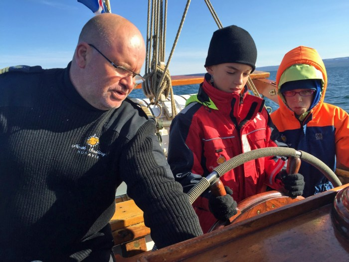 The author's children have a turn steering the boat, with the captain offering instruction