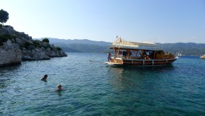The author's family swims in a sheltered bay with a picturesque boat nearby