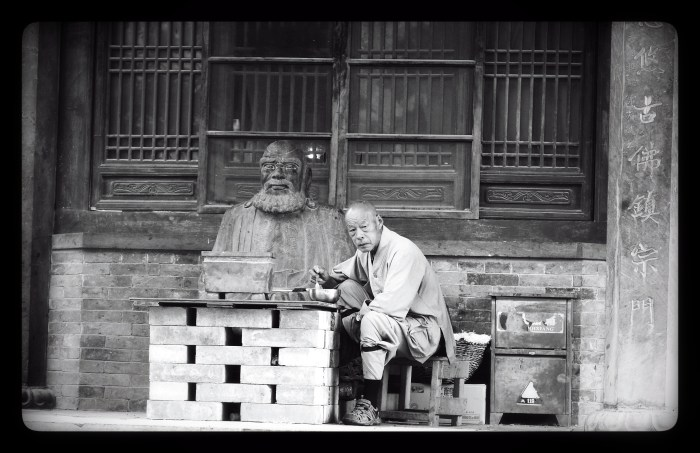 An elderly man sits at a makeshift table of bricks eating noodles in front of a statue of Buddha.