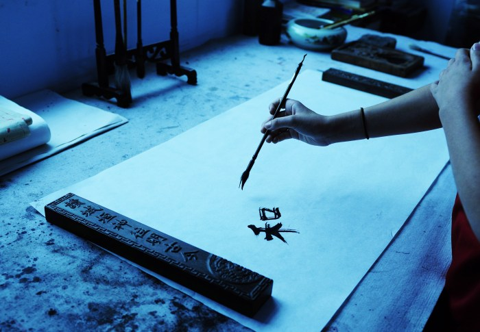 The author's daughter's hand writing Chinese characters with a calligraphy brush.
