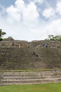 The author and her children raise their arms in victory halfway up a temple ruin