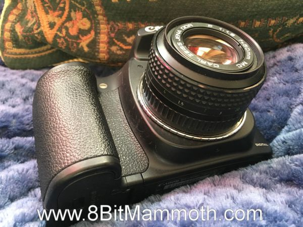 A photo of a Canon EOS 20D with a a Praktica Bayonet lens attached using an adapter.