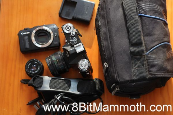A photo of two cameras, lens and related items.