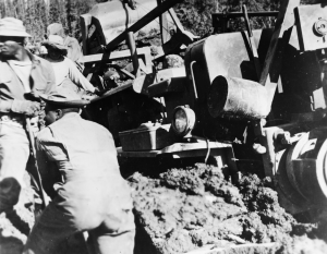 Black soldiers working on freeing a D8 dozer buried in mud on the Alaska Highway. 1942