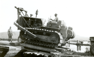 A Black Soldier operating a D8 bulldozer onto a barge crossing the Tagish River 1942.