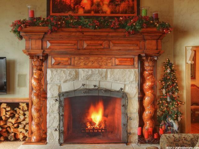 Very detailed fireplace with holiday decorations and a painting over the hearth.