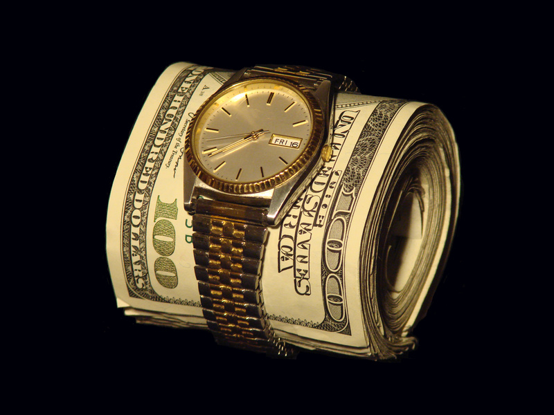 Watch around a roll of 100 dollar bills
