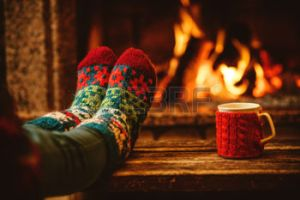 The eighth joy is sitting by a fire wearing colorful and festive socks.