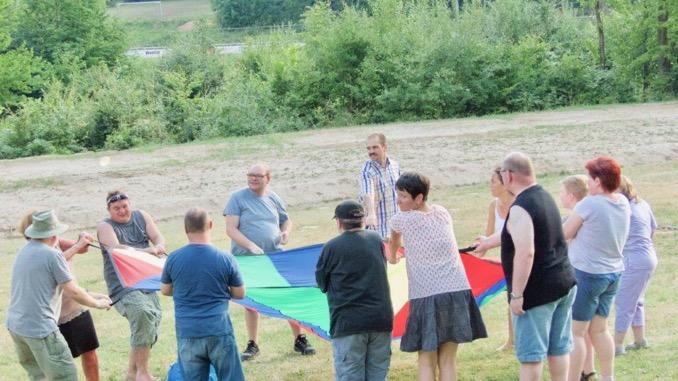 Gäste des Lebenshilfe-Sommerfestes spielen mit dem Fallschirm verschiedene Spiele. Zu sehen sind die Gäste, die einen bunten Fallschirm schwingen.