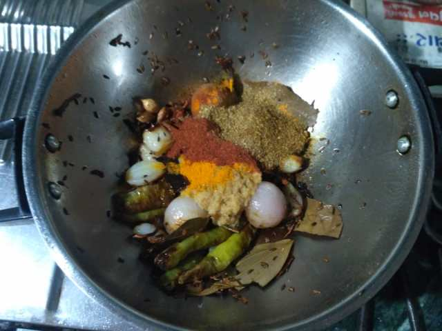 7. Add Ginger Garlic pastes, Turmeric, Red Chilli Powder, Coriander Powder (Dhaanna), Cumin powder, and a pinch of Garam Masala.