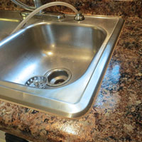 Caulking sink after Giani Granite Paint - The DIY Girl