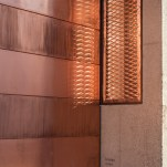 The main facade towards the street is defined by three large openings for transformers, which are each closed off with a reversible copper-sheet cladding.