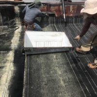 men repairing a flat roof