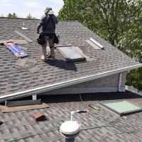 a man repairing a roof and skylight