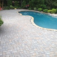 stone installation around the pool in the yard