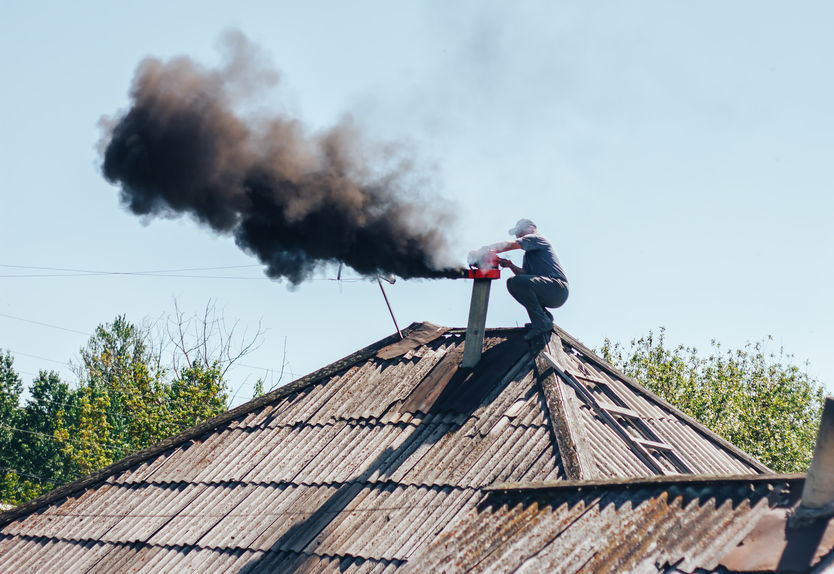 man doing a chimney sweep on an old house